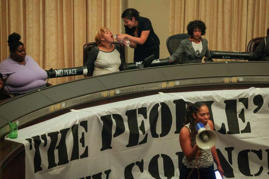 "Protesters hold a ""People's Council"" after taking over the Oakland City Council chambers Tuesday night. Photo: Sam Wolson / Special To The Chronicle / ONLINE_YES"