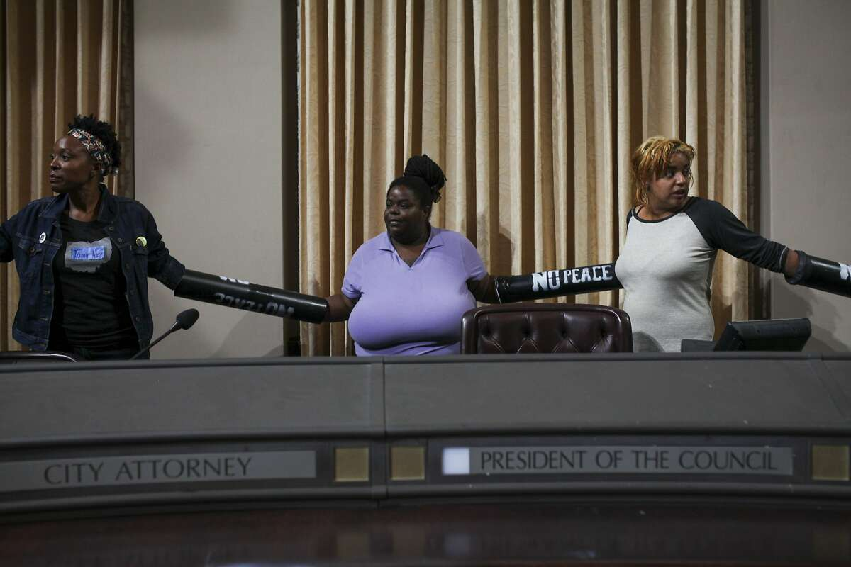 From left to right April Martin, Vanessa Riles and Erika Bell prepare sit in the Oakland city council chamber seats in support of affordable housing and against police brutality on May 5, 2015. Protesters took over a city council meeting and continued to occupy the space following the meeting.