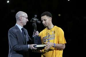 Stephen Curry (30) recieves his Kia NBA MVP trophy from NBA Commissioner Adam Silver before the game Tuesday. The Golden State Warriors played the Memphis Grizzlies at Oracle Arena in Oakland, Calif., in Game 2 of the Western Conference Semifinals on Tuesday, May 5, 2015.