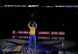 Stephen Curry (30) holds up his Kia NBA MVP trophy before game on Tuesday. The Golden State Warriors played the Memphis Grizzlies at Oracle Arena in Oakland, Calif., in Game 2 of the Western Conference Semifinals on Tuesday, May 5, 2015.