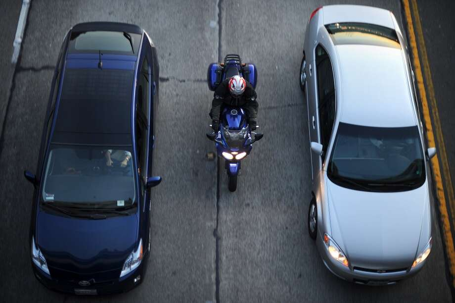 A motorcyclist lane splitting in the Bay Area. Photo: Noah Berger, Special To The Chronicle