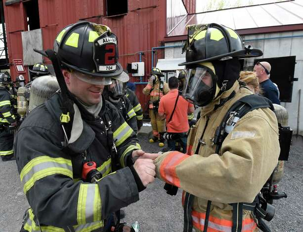 Buffalo Assemblyman Sean Ryan, right, is assisted in getting his turn-out gear on by Albany Firefighter Adam Mason during the Fire Ops 101 program held at the Municipal Training Center Tuesday May 5, 2015 in Colonie, N.Y.    (Skip Dickstein/Times Union) Photo: SKIP DICKSTEIN / 00031714A