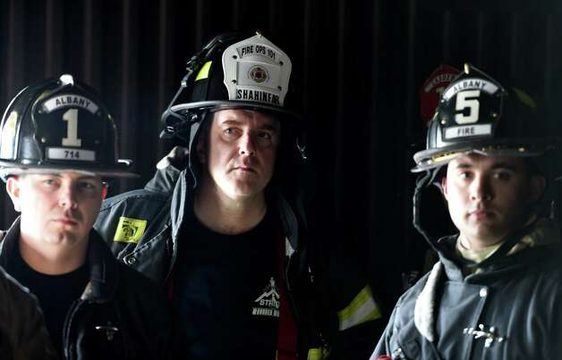 Albany Treasurer Darius Shahinfar, center is instructed on how to survive in a  burn room during the Fire Ops 101 program held at the Municipal Training Center Tuesday May 5, 2015 in Colonie, N.Y.    (Skip Dickstein/Times Union) Photo: SKIP DICKSTEIN / 00031714A