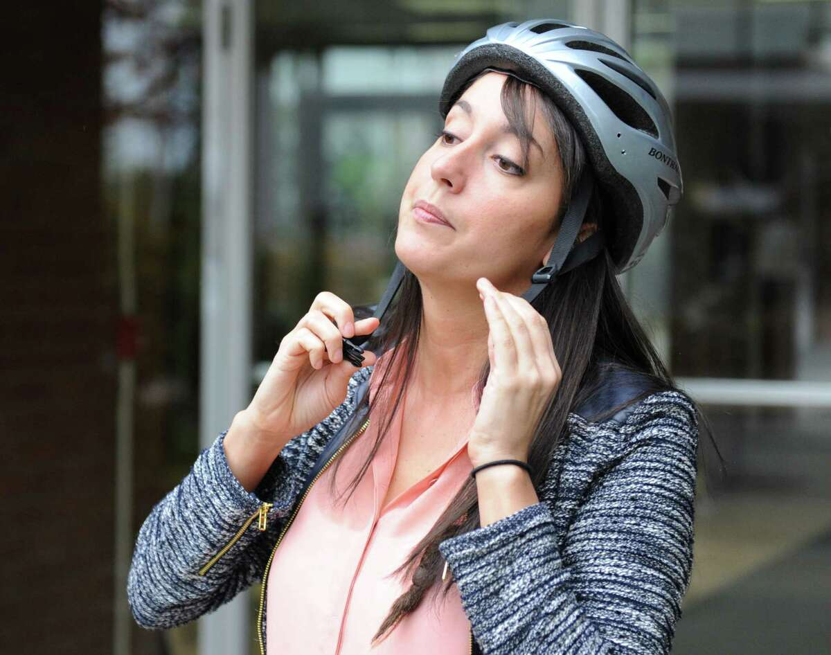 Stamford resident Mallory Arents puts her helmet on before riding her bike in Stamford, Conn. Wednesday, May 6, 2015. Arents commutes 4.6 miles by bike from Stamford to her work at the Darien Library every day.