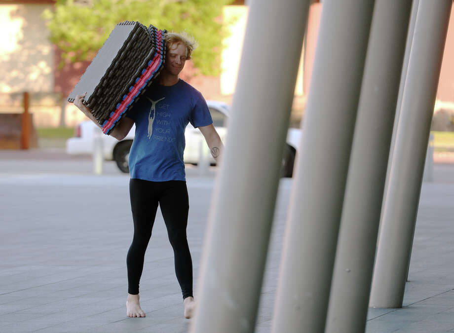 """Ian Lemasters carries mats from his vehicle to the Event Centre on Wednesday afternoon. Members of the Beaumont Acro-Yoga Community met Wednesday outside the Event Centre for a weekly """"jam"""" of acrobatics. Photo taken Wednesday 4/29/15 Jake Daniels/The Enterprise Photo: Jake Daniels / ©2015 The Beaumont Enterprise/Jake Daniels"""