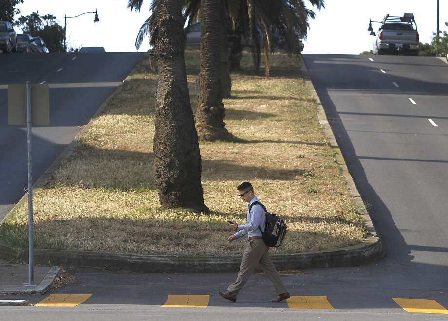 A man walks past the brown median strip at Dolores and 24th streets in San Francisco, Calif. on Wednesday, May 6, 2015. The city stopped watering the grassy strip to cutback on water consumption during the current drought crisis. Photo: Paul Chinn, The Chronicle