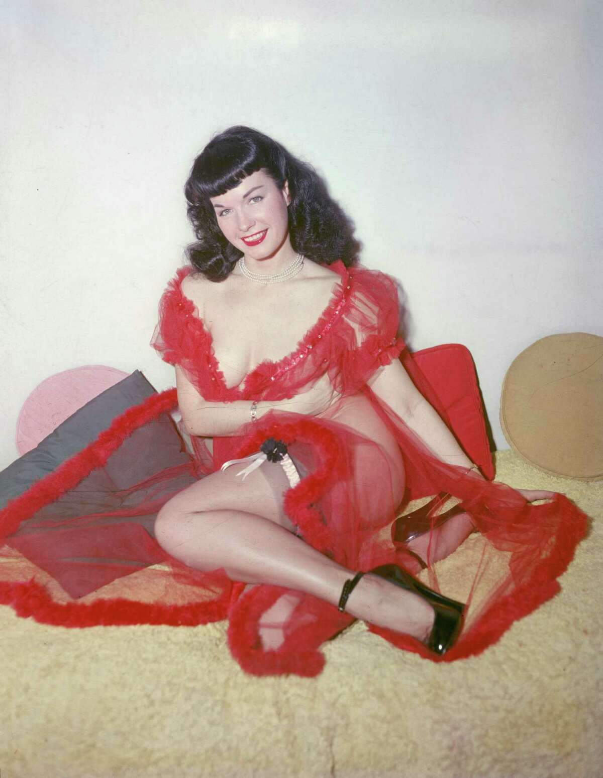 American glamour model and pin-up girl Bettie Page poses in a red negligee and stockings, circa 1955.