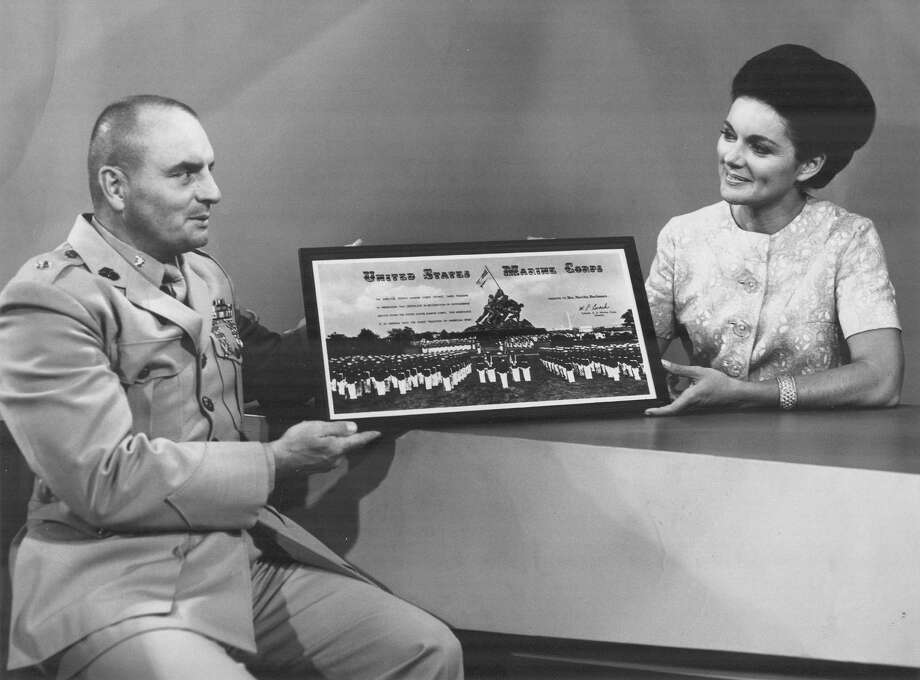 In this 1969 photo, Lt. Col. Fredrick McEwan presents an award of appreciation from the U.S. Marine Corps to Martha Buchanan, host of WOAI-TV's Early Evening Report, for assistance in acquiring clothing and baby bottles for a Vietnamese orphanage. Photo: Express-News Archives