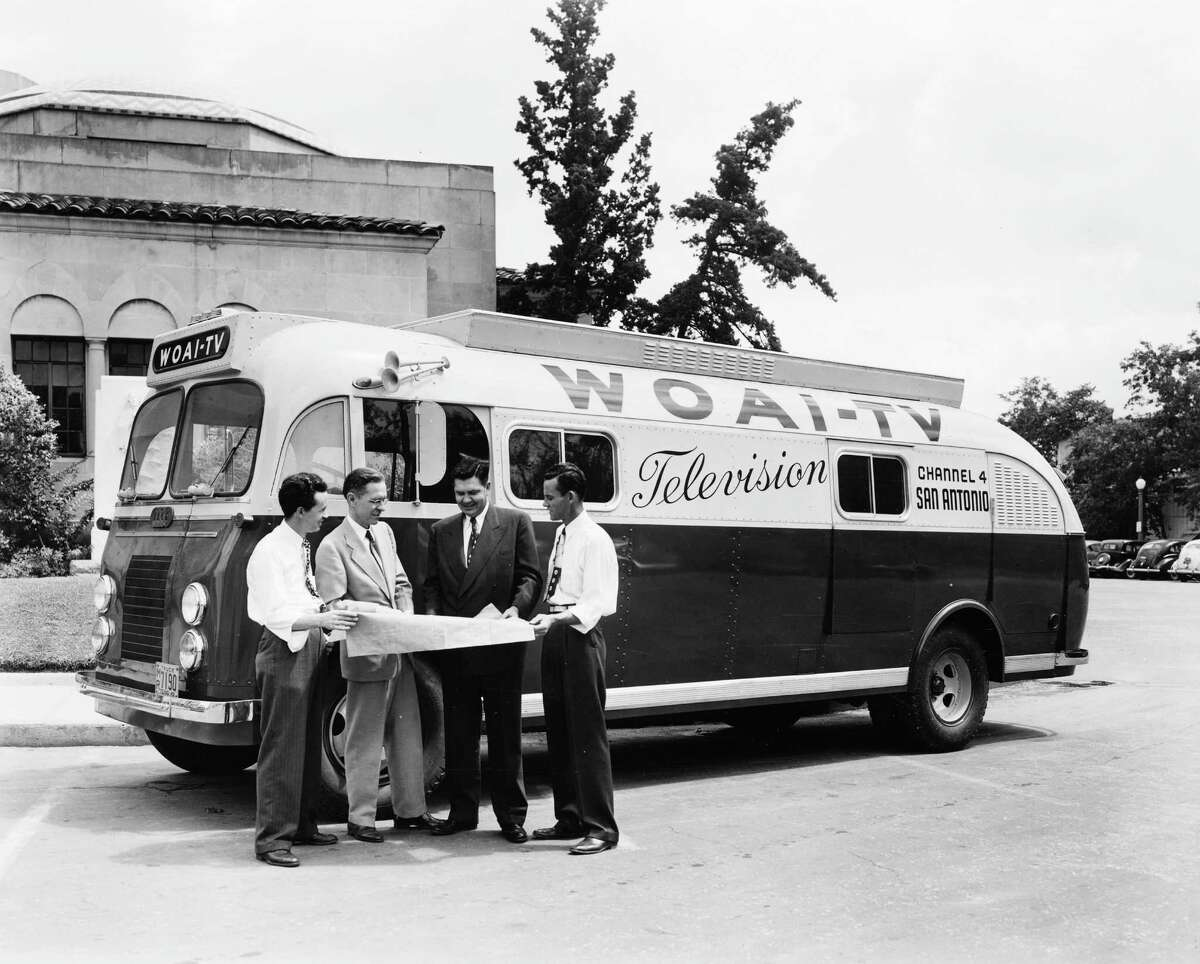 """WOAI-TV's """"mobile unit"""" is shown in this undated photo from the station's early days. According to a Sept. 1949 story from the Light, it was """"a bus-sized unit crammed with equipment"""" that included three field cameras. The men standing in front are unidentified, but second from the left may be program director J.R. Duncan. Photo credit:"""