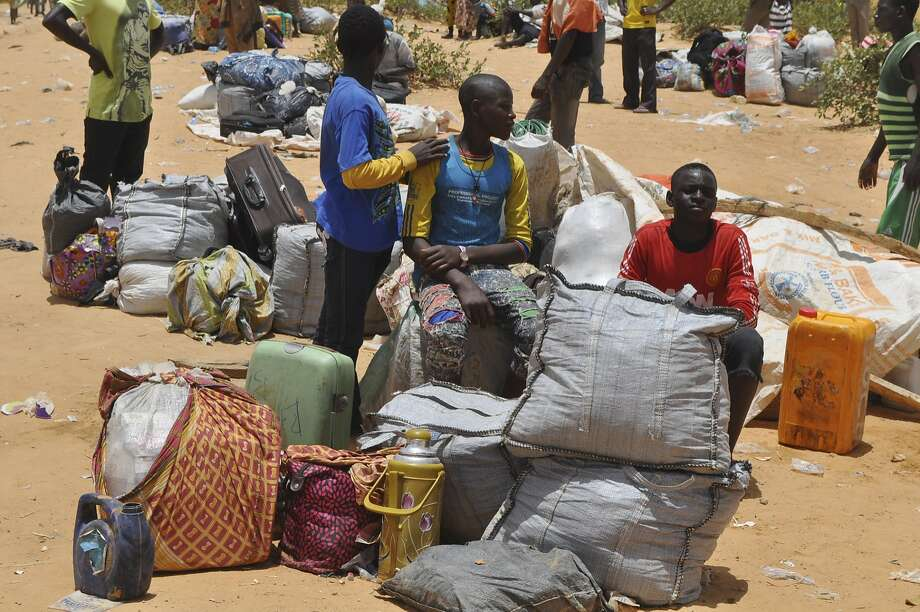Nigeria refugees sit with their belongings after being deported by Niger troops in Gaidam, Nigeria. Niger troops have deported more than 3,000 Nigerian fishermen and refugees escaping Boko Haram fighters. Photo: Jossy Ola, Associated Press