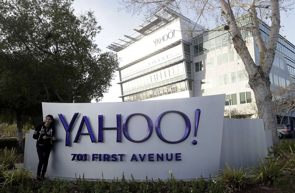 In this Jan. 14, 2015 photo, a visitor poses for photos in front of the Yahoo sign at the company's headquarters in Sunnyvale, Calif. Google, Yahoo and other major technology companies are far more inclined to hire Asians as computer programmers than to promote them to become managers or executives, according to a study released Wednesday, May 6, 2015. (AP Photo/Marcio Jose Sanchez)