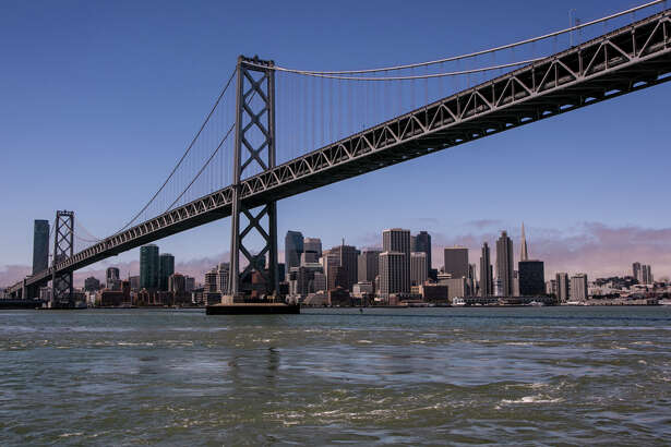 SAN FRANCISCO, CA - JULY 10:  The downtown San Francisco skyline and Bay Bridge are shown during a 30-minute ferry ride across to AT&T Park on July 10, 2013, in San Francisco, California.  Special ferry boats bring San Francisco Giants fans directly to AT&T Park during the baseball season.