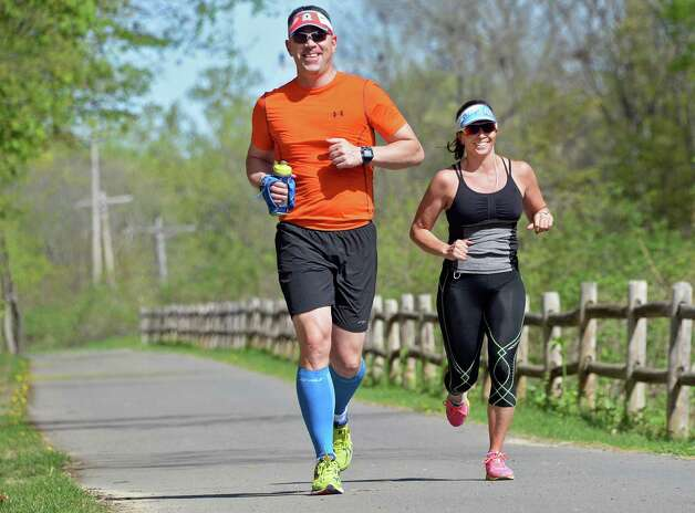 Running partners Eric Zenner, left, of Scotia and Antoinette Rose of Clifton Park are all smiles as they pass the halfway point of their 13-mile run along the bike path near Lock 8 Wednesday May 6, 2015 in Niskayuna, NY.  (John Carl D'Annibale / Times Union) Photo: John Carl D'Annibale