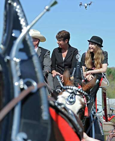 A drone is seen above horses pulling John Leavitt, left, Stephanie Palmatier and Sawyer Fredericks, right, at the end of a parade to the Fonda Speedway on Wednesday, May 6, 2015 in Fonda, N.Y. The 16-year-old singer/songwriter is one of the final six contestants on NBCOs show The Voice. John and Stephanie own the Heather Brooke Hill Clydesdales. (Lori Van Buren / Times Union) Photo: Lori Van Buren / 00031668A