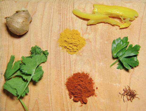 Ingredients for Moroccan dishes on Thursday, April 30, 2015, at Caroline Barrett's home in Delmar, N.Y. Clockwise from lower left is cilantro, ginger root, turmeric, preserved lemon, parsley, saffron and paprika. (Cindy Schultz / Times Union) Photo: Cindy Schultz / 00031596A