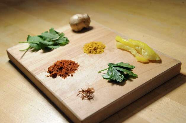 Ingredients for Moroccan dishes on Thursday, April 30, 2015, at Caroline Barrett's home in Delmar, N.Y. Clockwise from lower center is saffron, paprika, cilantro, ginger root, turmeric, preserved lemon and parsley. (Cindy Schultz / Times Union) Photo: Cindy Schultz / 00031596A