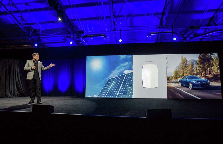 "Elon Musk, CEO of Tesla Motors Inc., unveils the company's new product called ""Powerwall"" in Hawthorne, Calif., Thursday, April. 30, 2015. Musk is trying to steer his electric car company's battery technology into homes and businesses as part of an elaborate plan to reshape the power grid with millions of small power plants made of solar panels on roofs and batteries in garages. (AP Photo/Ringo H.W. Chiu) Photo: Ringo H.W. Chiu / Associated Press / FR170512 AP"