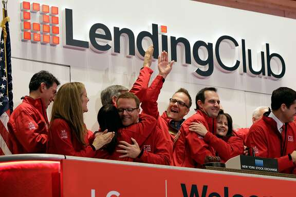 FILE - In this Dec. 11, 2014 file photo, Renaud Laplanche, third from right, Founder & CEO of Lending Club, embraces company CFO Carrie Dolan during opening bell ceremonies of the New York Stock Exchange, to mark Lending Club's IPO. Shares of Lending Club advanced 3 percent Wednesday, May 6, 2015, after the company reported better-than-expected results and upped its full-year outlook as more consumers discover peer-to-peer lending as an cheaper alternative to a traditional bank. (AP Photo/Richard Drew, File)