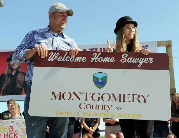 FultonvilleOs own Sawyer Fredericks, right, is presented a sign by Montgomery County Executive Matt Ossenfort before performing at the Fonda Speedway on Wednesday, May 6, 2015 in Fonda, N.Y. The 16-year-old singer/songwriter is one of the final six contestants on NBCOs show The Voice. (Lori Van Buren / Times Union) Photo: Lori Van Buren / 00031668A
