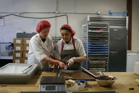 Claire Keane (l to r), owner, trains Marcella Lew for production in the production kitchen at Clairesquares on Tuesday, May 6, 2015 in Sausalito, Calif.