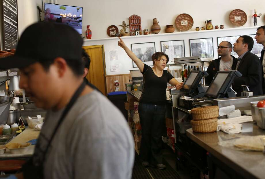 Veronica Salazar (center), owner, talks with customers as she works at the cash register during the lunch hour at El Huarache Loco on Tuesday, May 6, 2015 in Larkspur, Calif. Photo: Lea Suzuki, The Chronicle