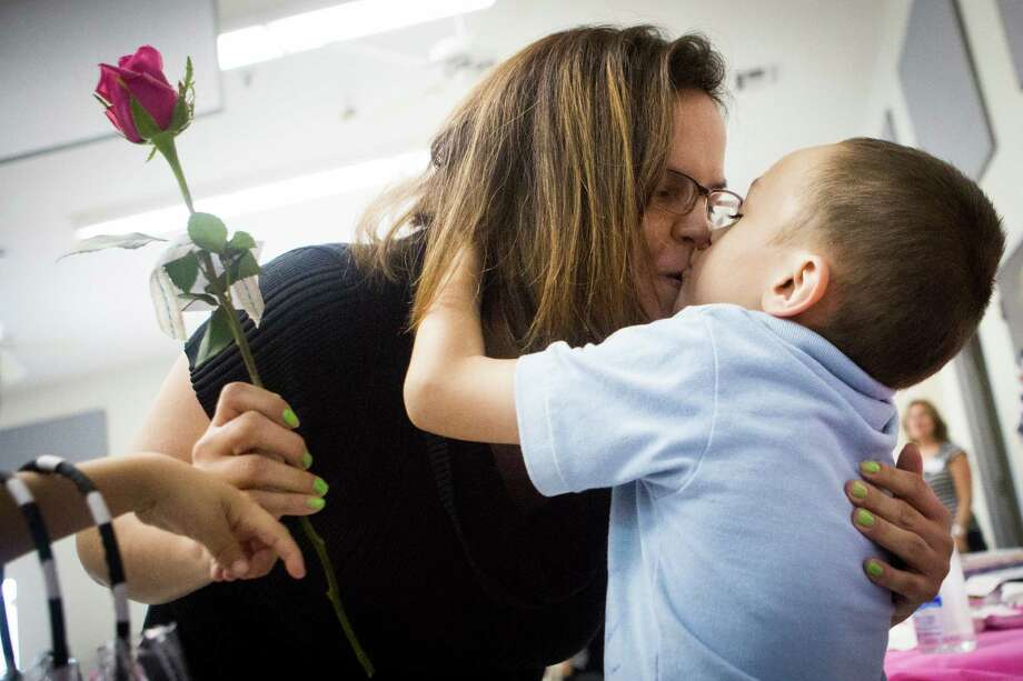 Chaz Dayton, 6, grabs his mother Angela Cole for a kiss after handing her a rose during an event hosted by Tress of Hope Guild on which about 30 homeless children presented their mothers with gifts ahead of Mother's Day, Wednesday, May 6, 2015, in Houston. Photo: Marie D. De Jesus, Houston Chronicle / © 2015 Houston Chronicle