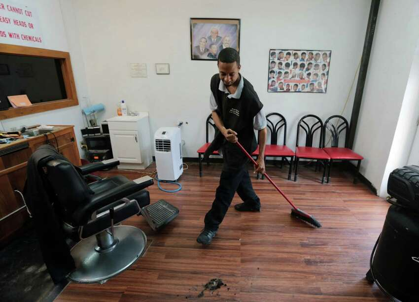 Russell Forest owner of Great News Barbershop works to clean up his small one chair shop that he opened five months ago in Prairie View, Texas, Wednesday May 6, 2015. Forest is a 2008 graduate of Prairie View A&M University.