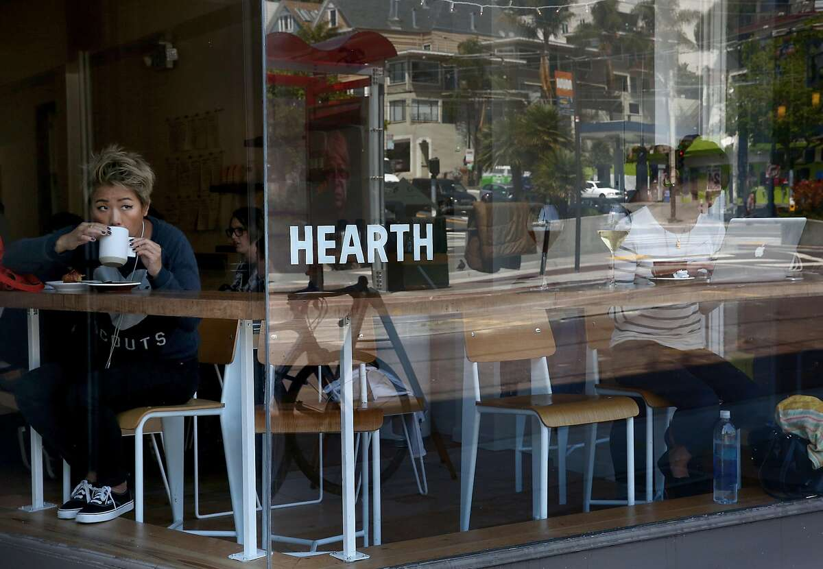 Kitty Yeung (left) has a jasmine tea and Brie en Croute as Jennifer Shalamanov (right) has a latte and almond and orange blossom croissant at Hearth Coffee Roasters in San Francisco, California, on Wednesday, May 6, 2015.