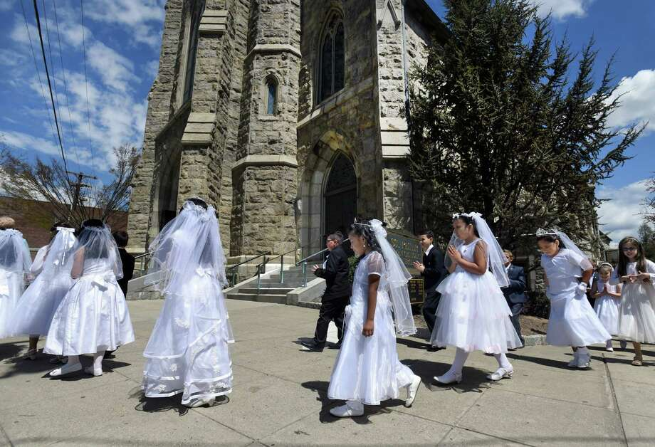 A procession of children walk to their First Communion at St. Peter Church in Danbury, Conn. on Saturday, May 2, 2015. Photo: Carol Kaliff / The News-Times