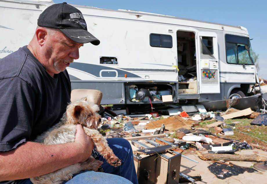 Damon Braley holds his parents' dog, Sammy, found the day after a storm hit Oklahoma City. Photo: Sue Ogrocki / Associated Press / AP