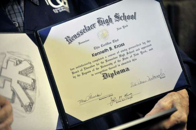 Navy veteran Ken Kross, an 87-year-old cancer patient, holds his high school diploma during a diploma ceremony at his residence at Van Rensselaer Heights apartments on Thursday, May 7, 2015, in Rensselaer, N.Y.  Kross dropped out of Rensselaer High School more than 70 years ago and never received a diploma.  Kross had enlist in the military and serve during World War II. (Paul Buckowski / Times Union) Photo: PAUL BUCKOWSKI / 00031756A