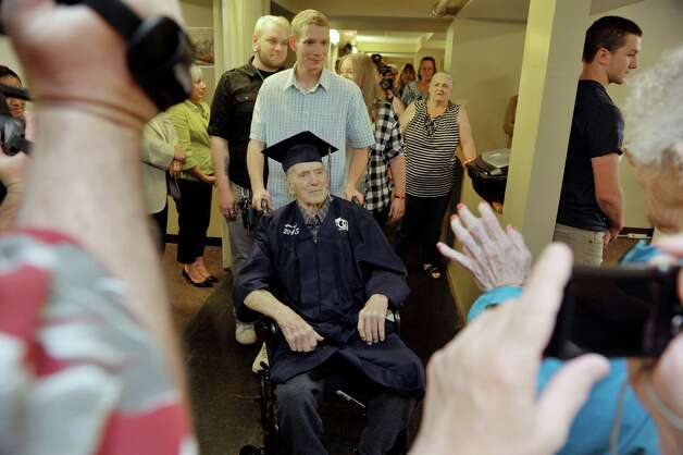 Luke Cotugno pushes the wheelchair with his grandfather, Navy veteran Ken Kross, an 87-year-old cancer patient,  during a diploma ceremony at his residence at Van Rensselaer Heights apartments on Thursday, May 7, 2015, in Rensselaer, N.Y.  Kross dropped out of Rensselaer High School more than 70 years ago and never received a diploma.  Kross had enlist in the military and serve during World War II. (Paul Buckowski / Times Union) Photo: PAUL BUCKOWSKI / 00031756A