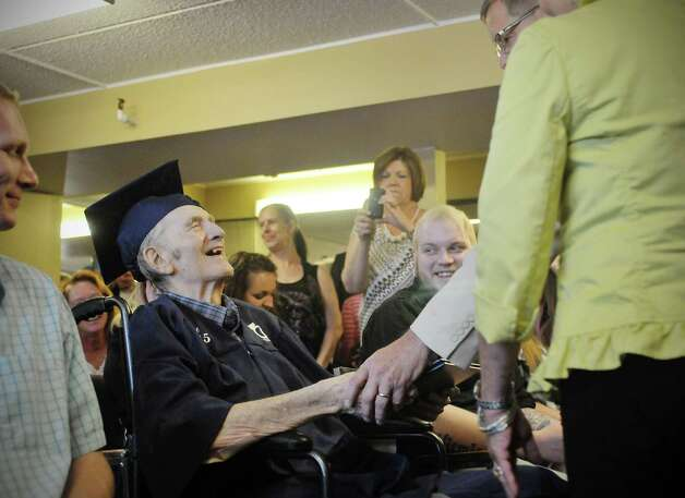 Navy veteran Ken Kross, an 87-year-old cancer patient, is congratulated during a diploma ceremony at his residence at Van Rensselaer Heights apartments on Thursday, May 7, 2015, in Rensselaer, N.Y.  Kross dropped out of Rensselaer High School more than 70 years ago and never received a diploma.  Kross had enlist in the military and serve during World War II. (Paul Buckowski / Times Union) Photo: PAUL BUCKOWSKI / 00031756A