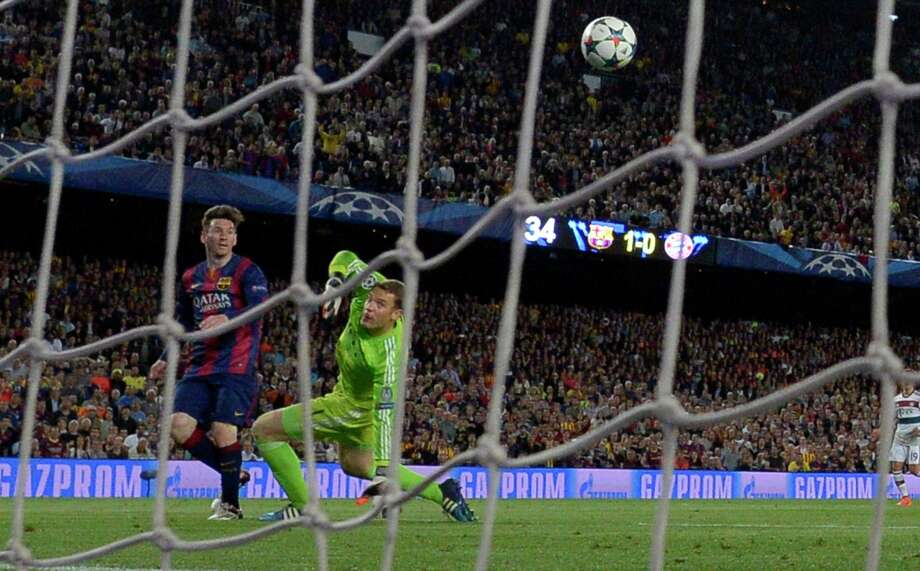 Barcelona's Argentinian forward Lionel Messi (L) scores his second goal during the UEFA Champions League football match FC Barcelona vs FC Bayern Muenchen at the Camp Nou stadium in Barcelona on May 6, 2015.     AFP PHOTO/ LLUIS GENELLUIS GENE/AFP/Getty Images Photo: LLUIS GENE / AFP / Getty Images / AFP