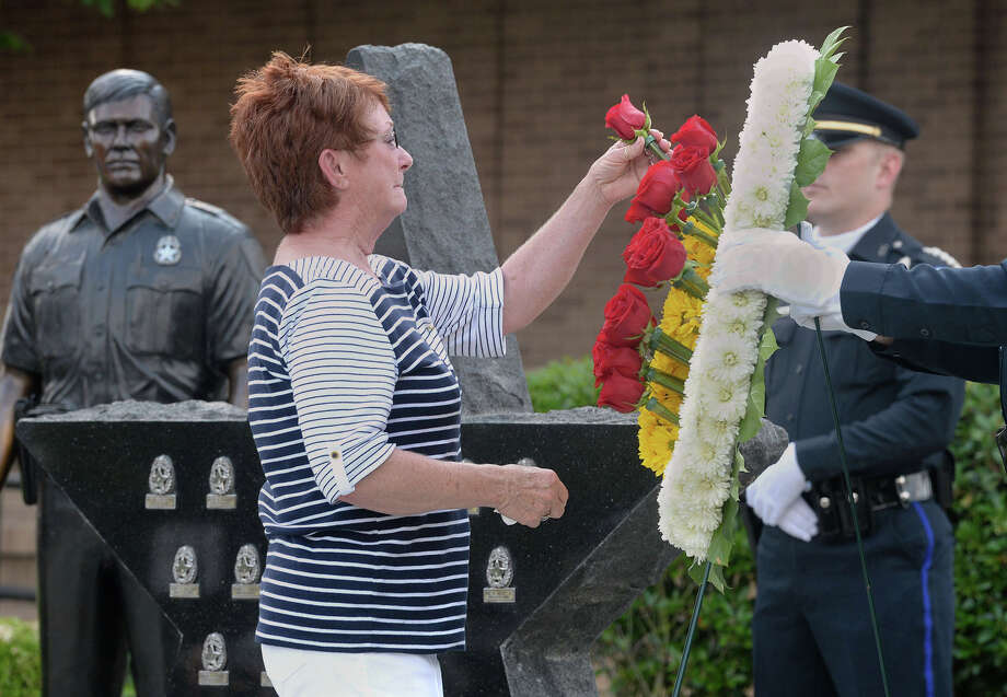 Billie Swann places a rose for Officer Lisa Beaulieu during a memorial service at the Beaumont Police station on Thursday. The service was conducted to honor officers who died in the line of duty. Beaulie was struck by a car and killed in 2007.
