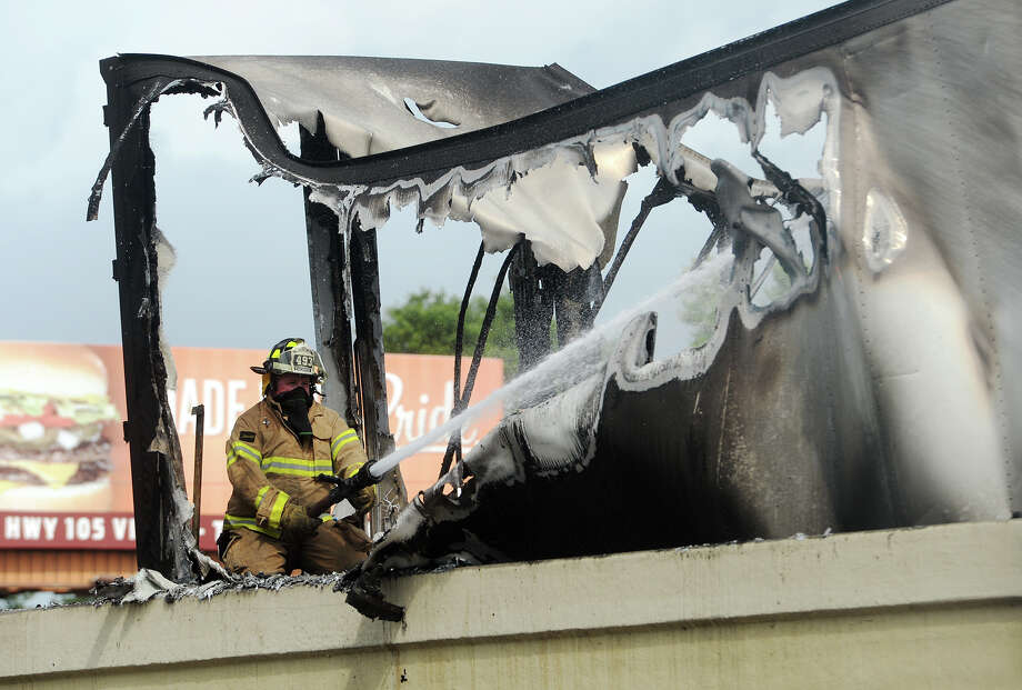 A firefighter sprays the inside of a burned out tractor trailer with water Thursday. A tractor trailer caught fire in the westbound lanes of I-10 just after Exit 859 on Thursday afternoon. Photo taken Thursday 5/7/15 Jake Daniels/The Enterprise Photo: Jake Daniels / ©2015 The Beaumont Enterprise/Jake Daniels