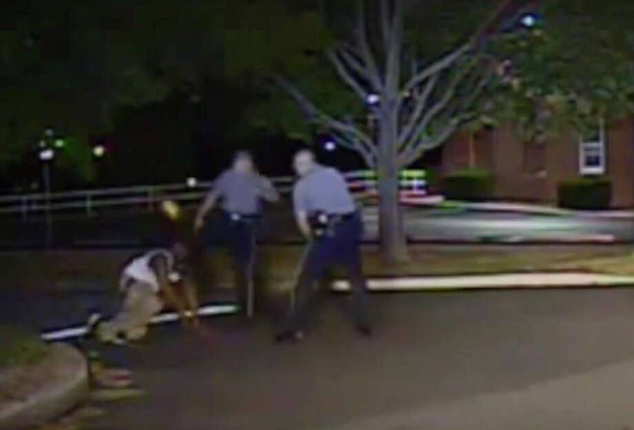An image from the video that shows Police Cpl. Thomas Webster (center) kicking Lateef Dickerson. Photo: Associated Press / Dover Police Department