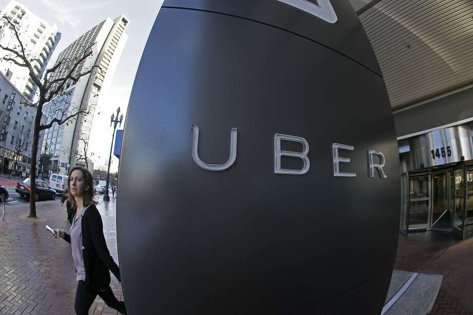 FILE--In this file photo taken, Dec. 16, 2014, a woman leaves the headquarters of Uber in San Francisco, Calif.  The Portland, Ore., City Council is expected to OK allowing Uber to operate legally while removing fare limits for traditional taxi companies with Uber drivers getting background checks and insurance. (AP Photo/Eric Risberg, file) Photo: Eric Risberg, Associated Press