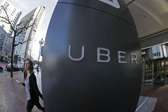 FILE--In this file photo taken, Dec. 16, 2014, a woman leaves the headquarters of Uber in San Francisco, Calif.  The Portland, Ore., City Council is expected to OK allowing Uber to operate legally while removing fare limits for traditional taxi companies with Uber drivers getting background checks and insurance. (AP Photo/Eric Risberg, file)