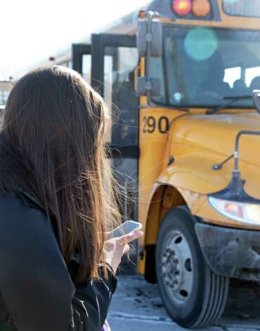 A student uses her smart phone while waiting for her bus at Guilderland High School Friday March 6, 2015, in Guilderland Center, NY.  (John Carl D'Annibale / Times Union) Photo: John Carl D'Annibale / 00030916A
