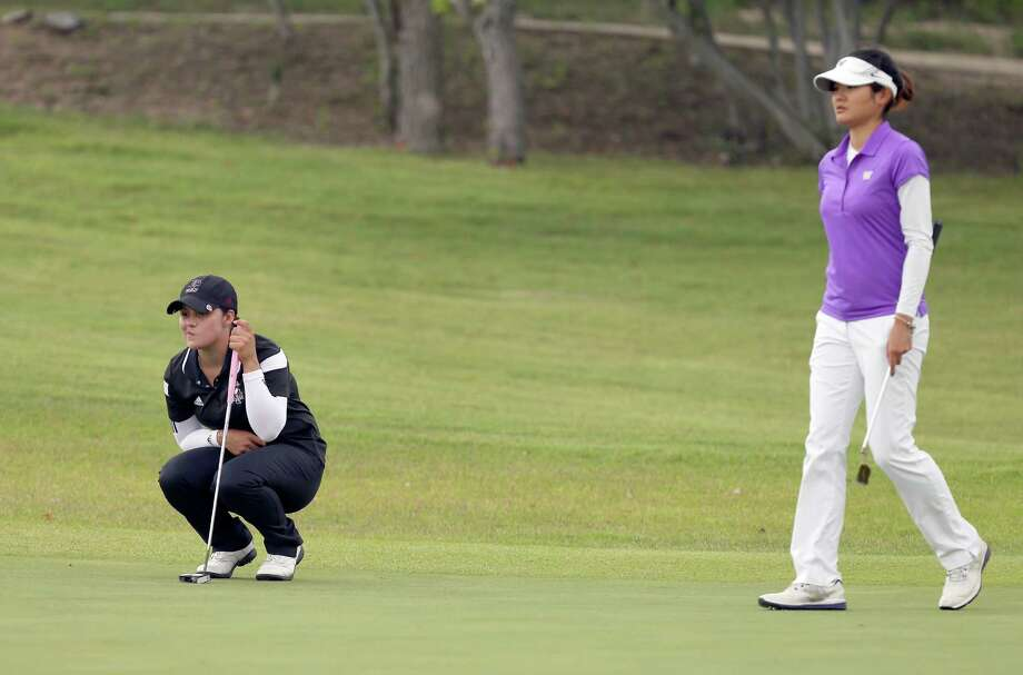 Texas A&M's Marijosse Navarro (left), who attended school in San Antonio, reads a putt as Ying Luo looks on at Briggs Ranch. Photo: William Luther / San Antonio Express-News / © 2015 San Antonio Express-News