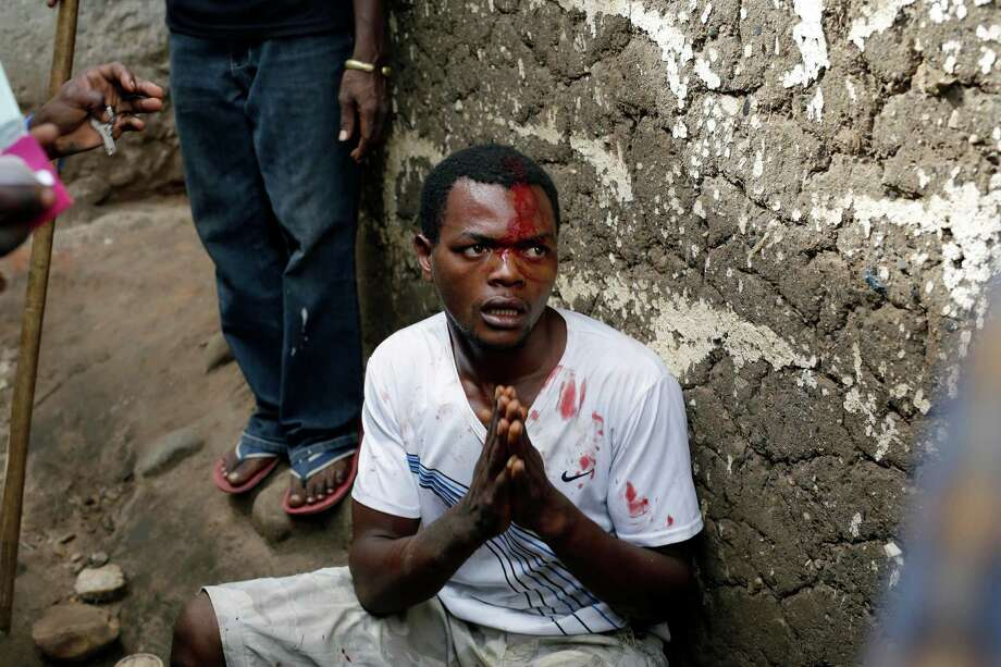 Jean Claude Niyonzima, a suspected member of the ruling party's Imbonerakure youth militia, pleads for his life as he is surrounded at his house by demonstrators protesting President Pierre Nkurunziza's decision to seek a third term in office in the Cibitoke district of Bujumbura, Burundi, Thursday May 7, 2015. At least one protestor has died in clashed with the widely feared Imbonerakure militias and police, sending scores to the streets seeking revenge. This suspect eventually managed to flee under a hail of stones into a covered sewer, where he remained till the army fired shots into the air to disperse the crowd.(AP Photo/Jerome Delay) Photo: Jerome Delay, STF / Associated Press / AP