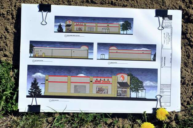 Artists renditions of what the new Family Dollar store will look like are seen at a groundbreaking for the store in Albany's South End on Thursday, May 7, 2015, in Albany, N.Y.  The 8,320 square-foot store will be open in the fall before the holidays and will employ between 10 and 12 people.  The store will being interviewing candidates for jobs about three weeks before the store opens and will advertise when the interviews begin.  The current building on the site will be knocked down and the ground will be raised to street level before a new building is constructed.  Vanguard-Fine Commercial Real Estate is the developer on the project.  Family Dollar has 8,000 stores nationwide.  (Paul Buckowski / Times Union) Photo: PAUL BUCKOWSKI / 00031720A