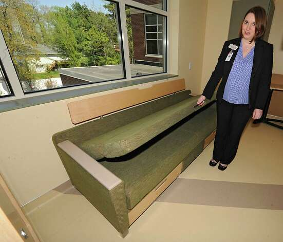 Carrie Boling, director patient access, demonstrates how a couch next to a patient bed folds down to be a twin bed in a room in the new Marylou Whitney and Desmond DelGiacco, MD Intensive Care Unit at Saratoga Hospital on Thursday, May 7, 2015 in Saratoga Springs, N.Y. (Lori Van Buren / Times Union) Photo: Lori Van Buren / 00031673A