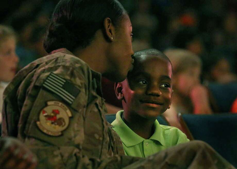 Air Force Staff Sergeant Lorelle Farrell who has been on her second deployment in Afghanistan, gives a kiss to her son Amari Davis, a second-grader at Green Valley Elementary School, during a school outing to the Magik Theatre, on Thursday, May 7, 2015. Davis was all smiles as his mother surprised him in front of some 600 other students there for a performance. Photo: Bob Owen / San Antonio Express-News / San Antonio Express-News