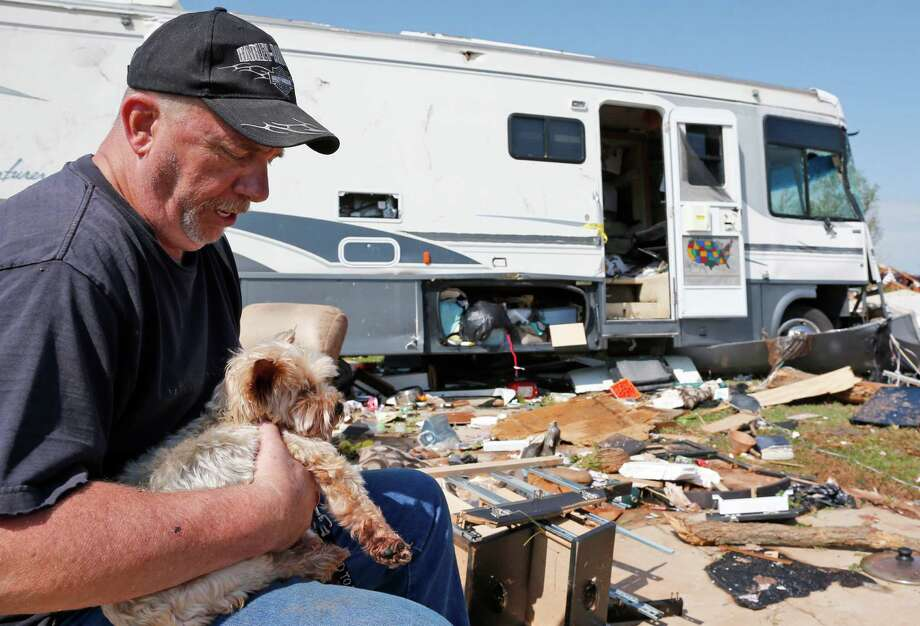 Damon Braley holds his parents' dog Sammy as he looks over the area where their recreational vehicle used to park in Oklahoma City. He said his parents both were taken to the hospital Wednesday after severe weather hit the area. Photo: Sue Ogrocki, STF / AP