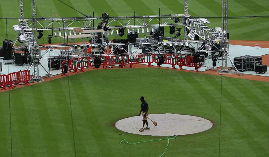 Astros groundskeeper Willie Berry helps prepare the Minute Maid Park playing surface for Saturday's HBO World Championship Boxing program. Photo: Mayra Beltran, Staff / © 2015 Houston Chronicle