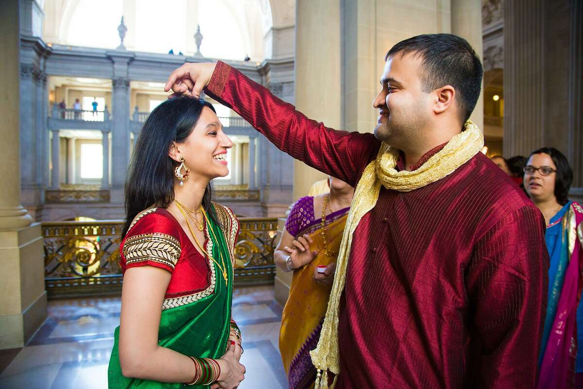Rohan Chaukulkar applies sindoor, the mark of a married woman in Hinduism, to Nandita Bhagwat's hair line at City Hall, Friday May 1, 2015, in San Francisco, CA.