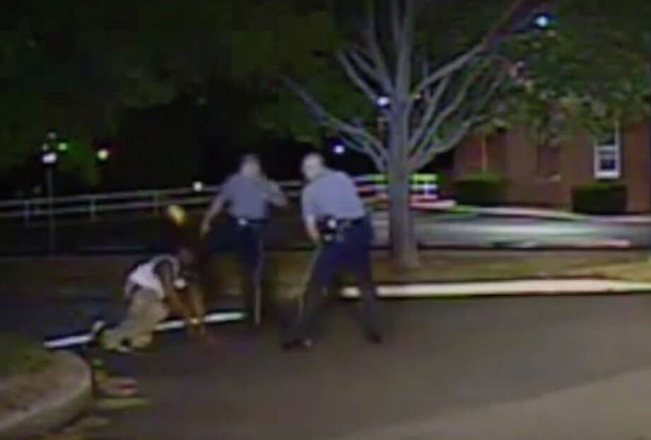 In this Aug. 24, 2013, photo made from a dash camera video and released by the Dover (Del.) Police Department, Cpl. Thomas Webster IV, center, kicks Lateef Dickerson as he responded to commands. Photo: HOGP / Dover Police Department