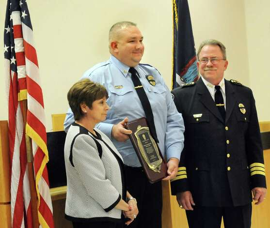 Frank Lawyer, senior public safety dispatcher, center, receives a distinguished service award from Supervisor Paula Mahan, left, and Chief Steven Heider during the Colonie Police Department awards ceremony on Thursday, May 7, 2015,  at the Colonie Public Safety Building in Colonie, N.Y. (Cindy Schultz / Times Union) Photo: Cindy Schultz / 00031750A